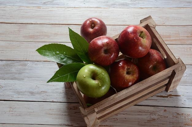 Frische rote und grüne äpfel in der holzkiste im rustikalen stil. gesundes essen Premium Fotos