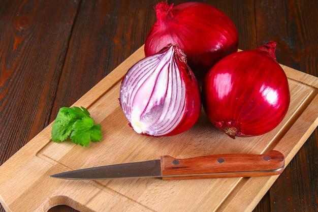 Frische rote zwiebeln und gehackte scheiben auf einem holztisch. Premium Fotos