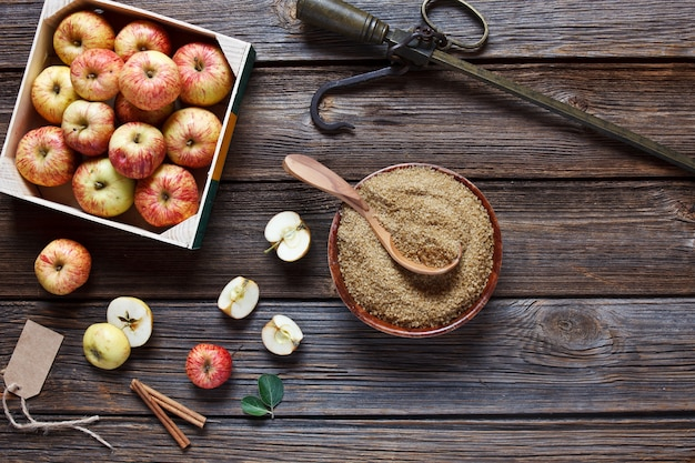 Frische saftige äpfel in holzkiste, steelyard, braunem zucker und zimtstangen Premium Fotos