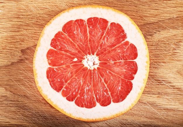 Frische saftige grapefruitscheiben auf holz Kostenlose Fotos