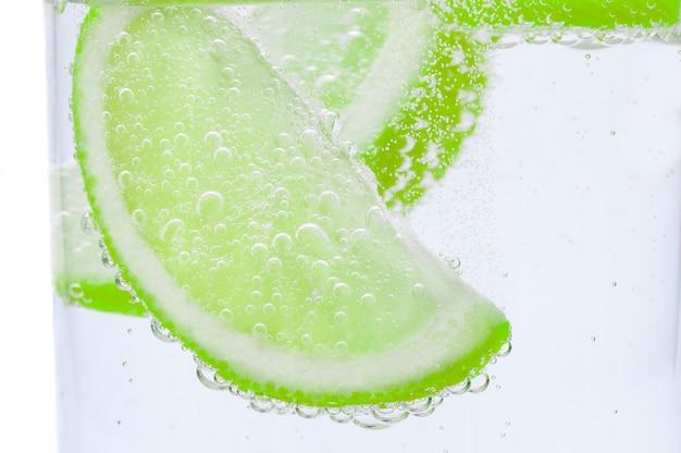 Frische saftige limetten sinken in kristallklares wasser. Premium Fotos