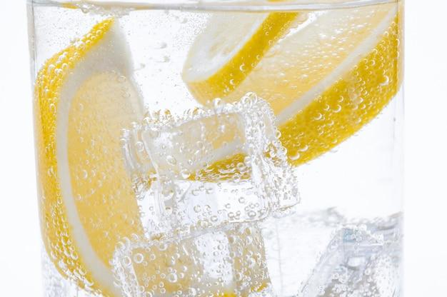 Frische saftige zitronenscheiben mit kristallklarem wasser in den cocktail geben. Premium Fotos