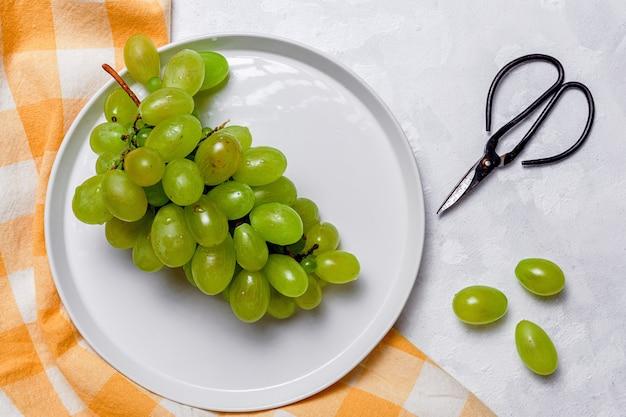 Frische saisonale trauben in plastikteller mit schere Premium Fotos