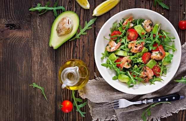 Frische salatschüssel mit garnelen, tomaten, avocado und rucola auf holztisch schließen oben. gesundes essen. sauberes essen. draufsicht. flach liegen. Premium Fotos