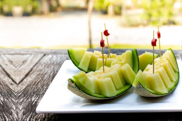 Frische scheibe süße grüne melone auf weißem taschentuch auf holztisch gelegt. Premium Fotos