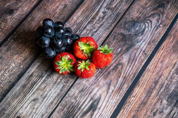 Frische schottische erdbeeren und schwarze trauben auf holztisch. Kostenlose Fotos