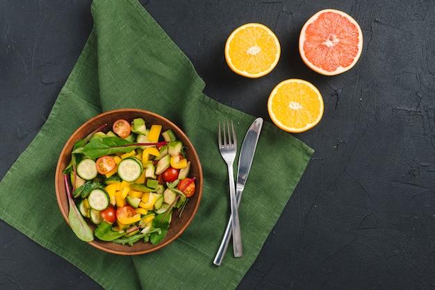 Frische schüssel gemüsesalat; orangen und pampelmusen auf schwarzem konkretem hintergrund Kostenlose Fotos