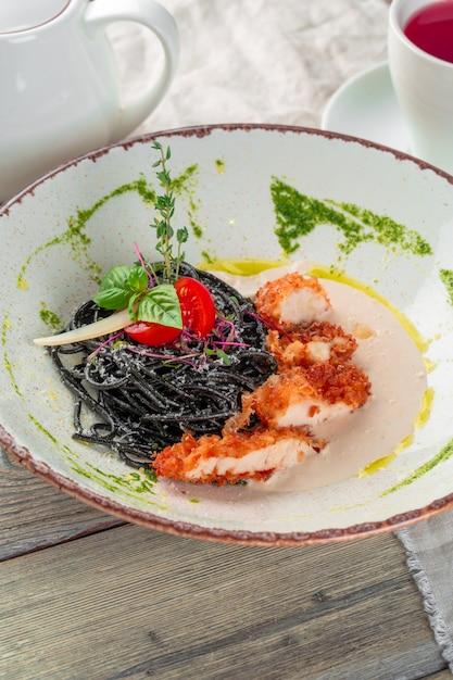 Frische schwarze taglioliniteigwaren mit huhn in den kräutern auf rucola und tomaten Premium Fotos