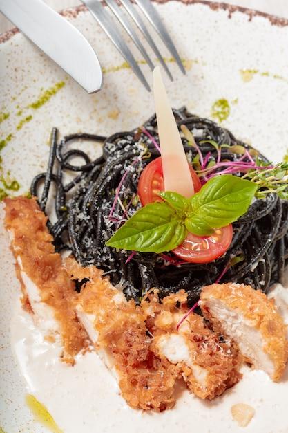 Frische schwarze taglioliniteigwaren mit huhn in den kräutern Premium Fotos