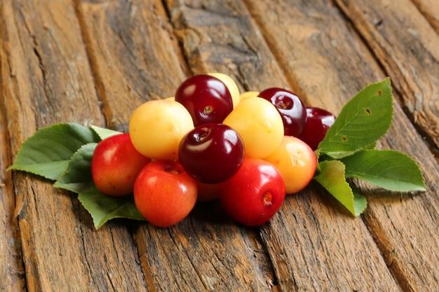 Frische süße kirschen auf alter hölzerner retro- weinlese Premium Fotos