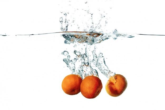 Frische tangerinefrüchte, die in wasserspritzen fallen Kostenlose Fotos