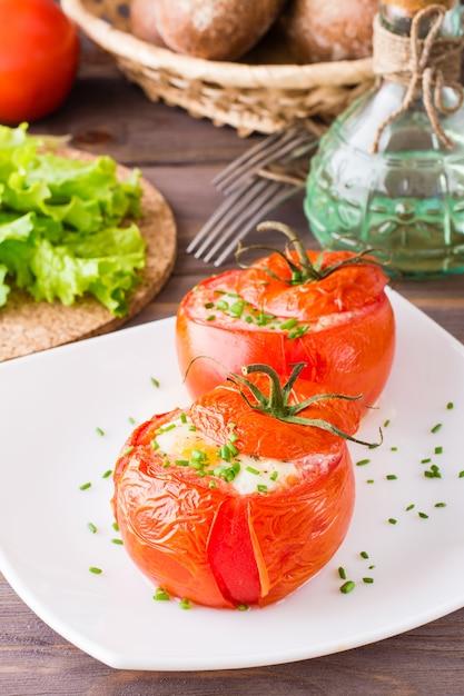 Frische tomaten backten mit dem käse und ei, die mit frühlingszwiebeln auf einer platte auf einem holztisch besprüht wurden Premium Fotos