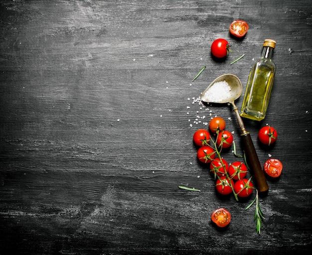 Frische tomaten mit olivenöl und einem löffel salz. Premium Fotos