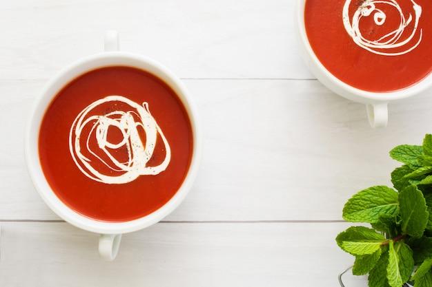 Frische tomatensuppe in einer weißen schüssel auf weißem draufsicht-kopienraum des holztischs Premium Fotos