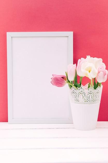 Frische tulpenblumen im vase mit leerem fotorahmen Kostenlose Fotos
