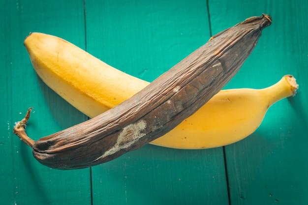 Frische und faule banane auf hölzernem hintergrund Kostenlose Fotos