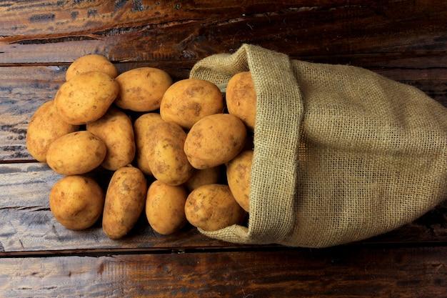 Frische und rohe kartoffeln geerntet von der plantage und in eine rustikale tasche auf holztisch gelegt Premium Fotos