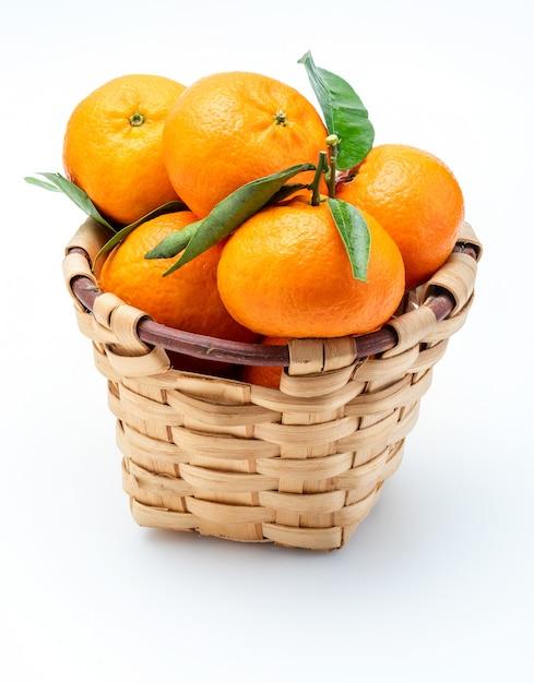 Frische und rohe mandarinen mit grünen blättern im rustikalen weidenkorb. Premium Fotos