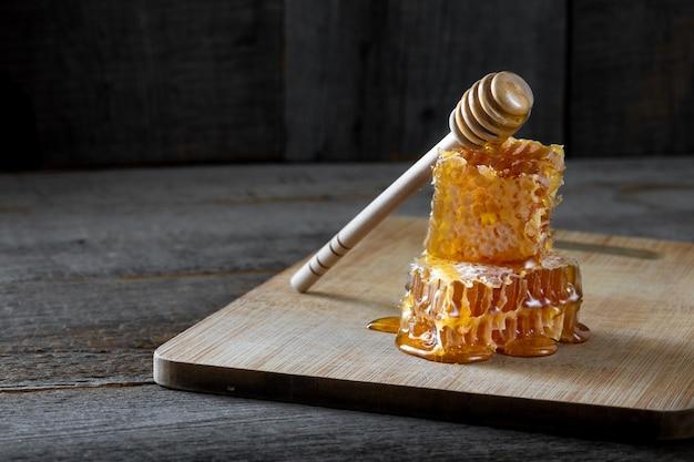 Frische wabenstücke mit honig und einem holzstab Premium Fotos