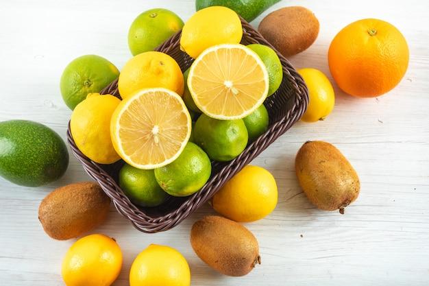Frische zitronen im korb umgeben mit zitrusfrüchten auf weißem hölzernem Kostenlose Fotos
