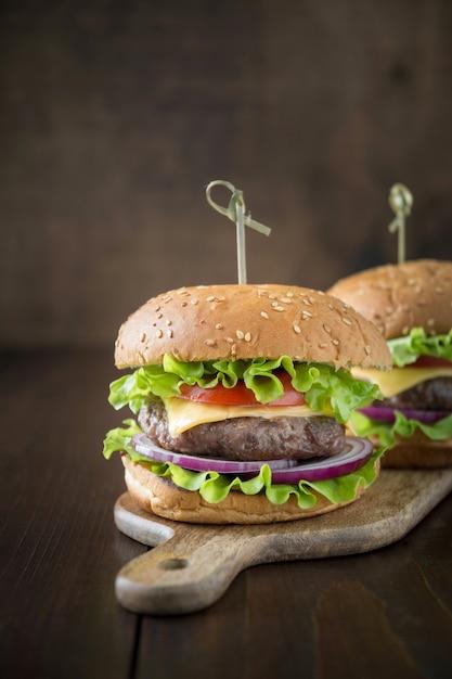 Frische zwei rindfleischburger mit gemüse auf hölzernem brett Premium Fotos