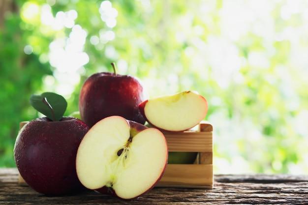 Frischer apfel in der holzkiste über grüner natur, frische frucht Kostenlose Fotos