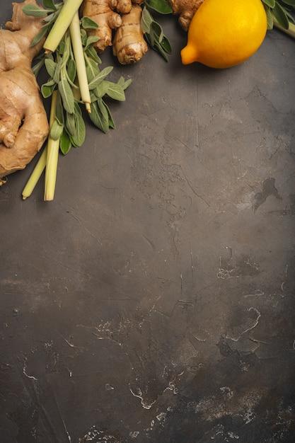 Frischer bestandteilingwer, zitronengras, salbei, honig und zitrone für gesunden antioxidans- und entzündungshemmenden ingwertee auf dunklem hintergrund mit kopienraum. ansicht von oben. Premium Fotos
