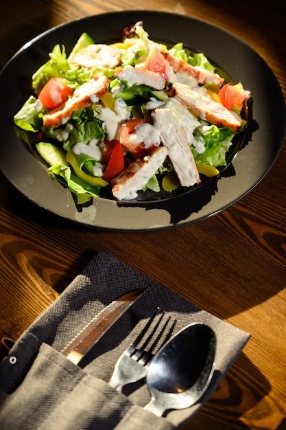 Frischer caesar-salat im schwarzblech auf dunklem holztisch. ansicht von oben. Premium Fotos