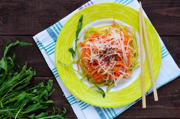 Frischer diät-fitness-salat von daikon-rettich, karotten, leinsamen, rucola. vegane küche. draufsicht Premium Fotos
