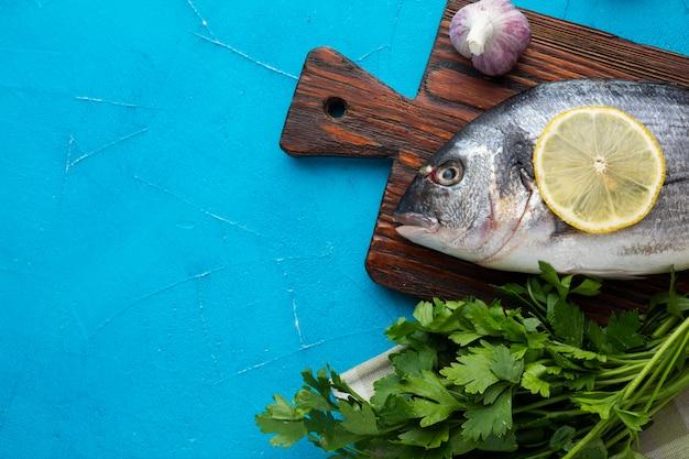 Frischer fisch der draufsicht mit zitrone Kostenlose Fotos