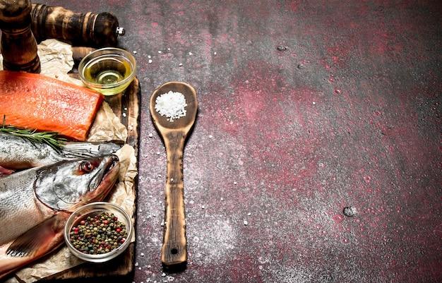 Frischer fisch mit einem stück filet und gewürzen auf rustikalem tisch. Premium Fotos