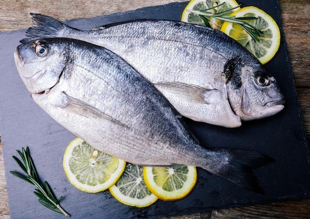 Frischer fisch mit zitrone auf rustikalem brett Kostenlose Fotos