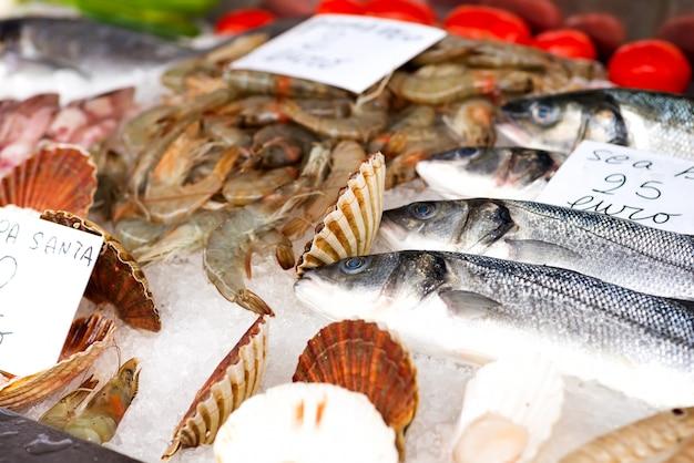 Frischer fisch, tintenfisch, tintenfisch und garnelen zum verkauf auf eis auf der theke Premium Fotos