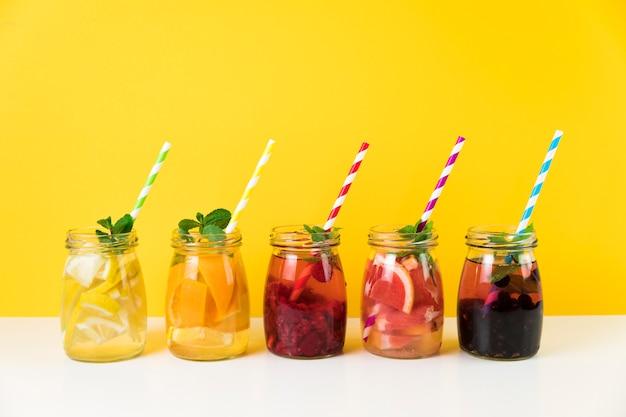 Frischer fruchtsaft mit gelbem hintergrund Premium Fotos