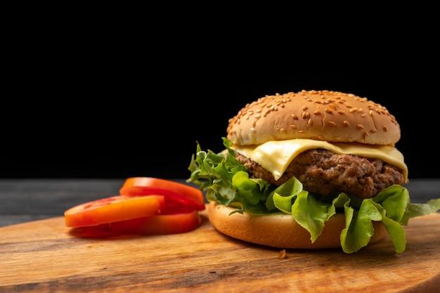Frischer geschmackvoller selbst gemachter hamburger mit frischgemüse auf einem schneidebrett. Premium Fotos