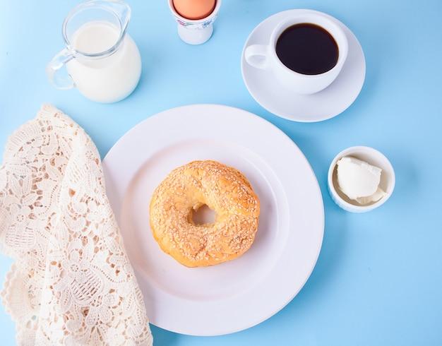Frischer gesunder bagel auf einer weißen platte mit tasse kaffee Premium Fotos