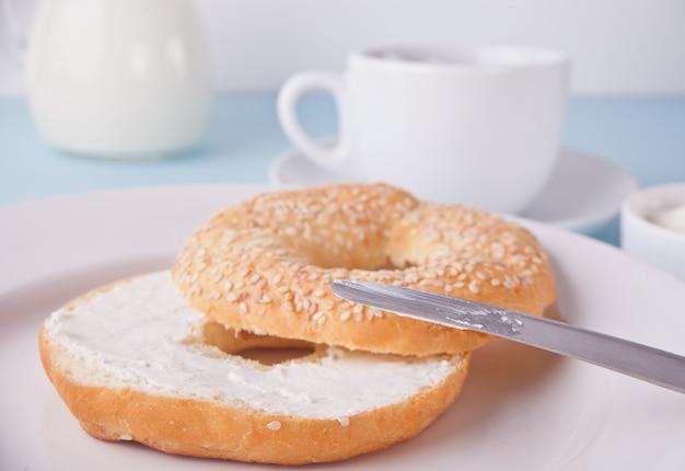 Frischer gesunder bagel auf einer weißen serviette mit tasse kaffee, frischkäse und eiern zum frühstück. Premium Fotos