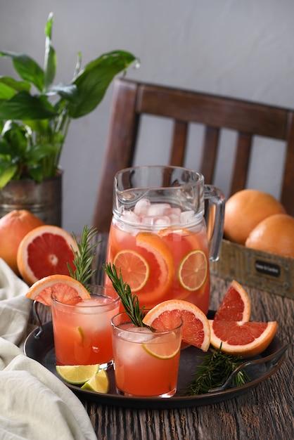 Frischer grapefruitcocktail. frischer sommercocktail mit grapefruit, limette, rosmarinzweig und eiswürfeln. Premium Fotos