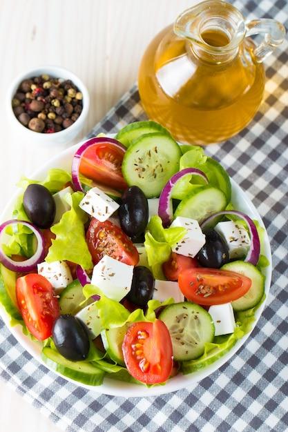 Frischer griechischer salat auf hölzernem hintergrund. Premium Fotos