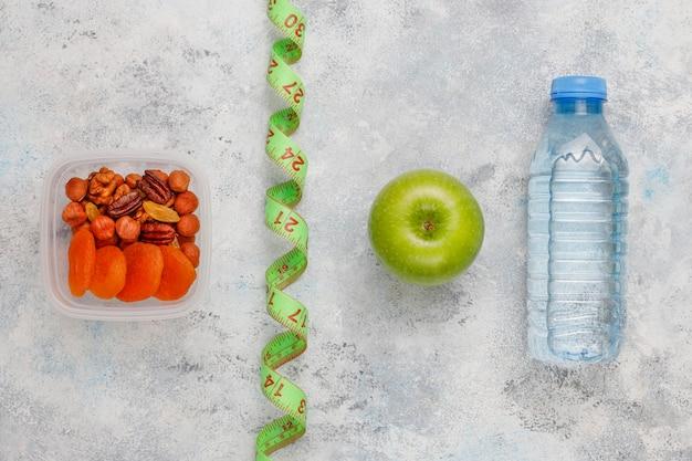 Frischer grüner apfel, maßband und flasche süßwasser auf grauem beton Kostenlose Fotos