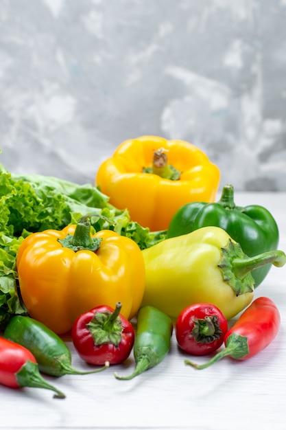 Frischer grüner salat zusammen mit farbigen paprika und würzigen paprika auf hellem schreibtisch Kostenlose Fotos
