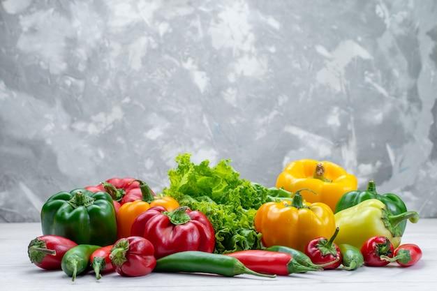 Frischer grüner salat zusammen mit farbigen paprika und würzigen paprika zusammensetzung auf hellem schreibtisch Kostenlose Fotos
