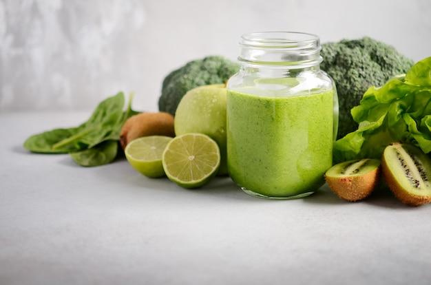 Frischer grüner smoothie in einem glas mit bestandteilen auf einem grauen konkreten hintergrund, selektiver fokus. Premium Fotos