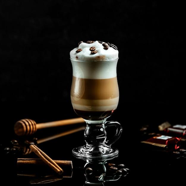 Frischer latte mit sahne und kaffeebohnen Kostenlose Fotos
