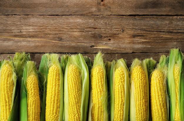 Frischer mais auf maiskolben auf rustikalem hölzernem der weinlese Premium Fotos