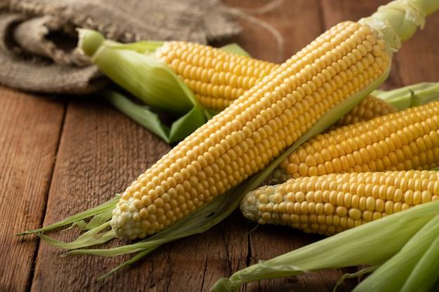 Frischer mais auf maiskolben auf rustikalem holztisch. Premium Fotos