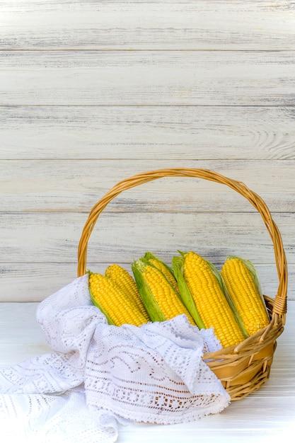 Frischer maiskolben im weidenkorb. unbehandelte maiskolben. frisches maisgemüse im korb. geernteter mais im weidenkorb, frisch gepflückte maisohren in landwirtschaftlicher feldlandschaft, selektiv Premium Fotos