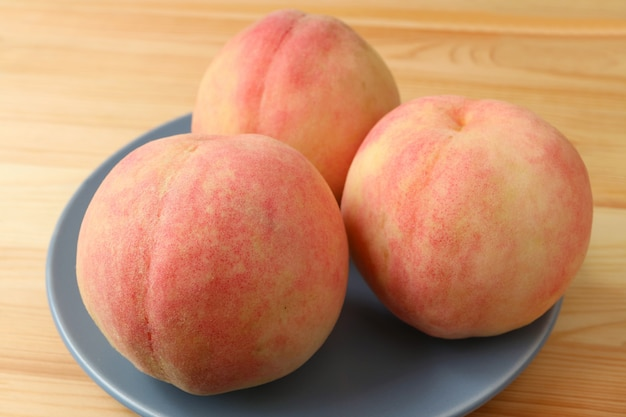 Frischer reifer pfirsich drei auf der blauen keramischen platte gedient auf holztisch. Premium Fotos