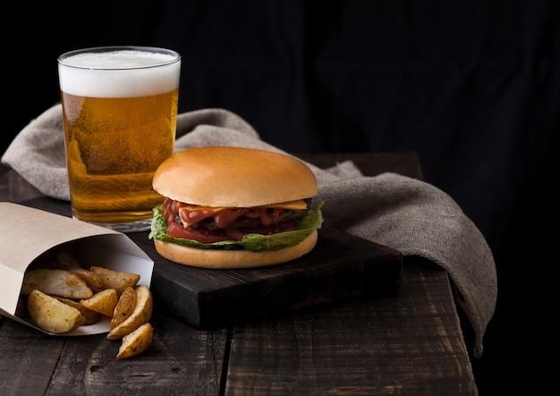 Frischer rindfleischburger mit kartoffelkeilen und glas bier auf hölzernem hintergrund Premium Fotos