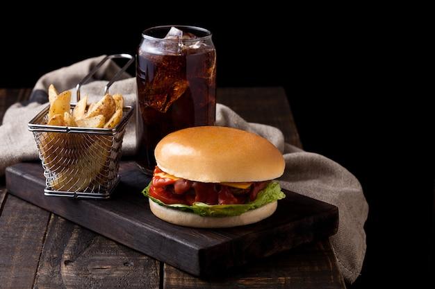 Frischer rindfleischburger mit kartoffelkeilen und glas cola soda trinken auf hölzernem hintergrund Premium Fotos